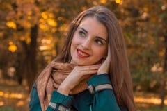 有红有嘴微笑的逗人喜爱的女孩和在面孔附近保留手 库存照片