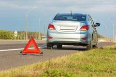 有红色三角标志的残破的汽车 免版税图库摄影