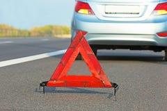 有红色三角标志的残破的汽车 免版税库存图片