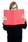 有红色专心书本知识的学员 免版税库存照片
