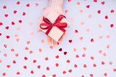 有红色丝带弓的工艺箱子在女性手上 浓缩的情人节 免版税库存照片