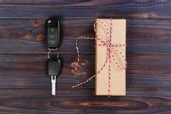 有红色丝带弓的汽车关键近的纸箱在木桌背景 圣诞节或华伦泰` s天礼物或当前抽象浓缩 库存照片
