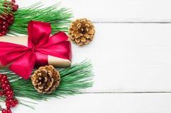 有红色丝带弓的礼物盒和分支与锥体的圣诞树在白色木葡萄酒背景 免版税库存照片