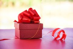 有红色丝带弓的礼物盒红顶视图自然红色当前箱子对圣诞快乐假日新年快乐或华伦泰的礼物的 免版税库存图片