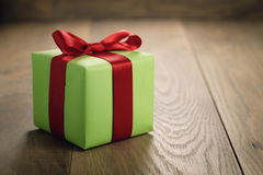 有红色丝带弓的简单的绿皮书礼物盒在与拷贝空间的橡木桌上 免版税库存图片