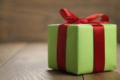 有红色丝带弓的简单的绿皮书礼物盒在与拷贝空间的橡木桌上 库存图片