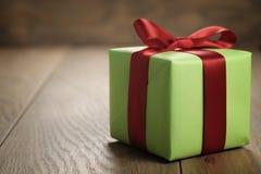 有红色丝带弓的简单的绿皮书礼物盒在与拷贝空间的橡木桌上 库存照片