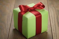 有红色丝带弓的简单的绿皮书礼物盒在橡木桌上 库存照片