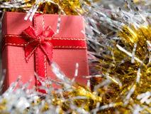 有红色丝带弓的红色礼物盒和银和金彩虹发光的装饰的金黄缝地方 圣诞节和新年conce 图库摄影