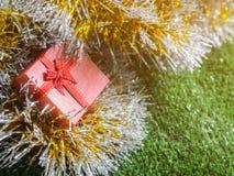 有红色丝带弓的红色礼物盒和银和金彩虹发光的装饰背景的金黄缝地方在绿草 库存图片