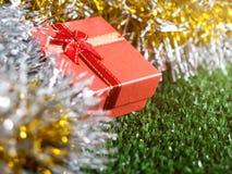 有红色丝带弓的红色礼物盒和银和金彩虹发光的装饰背景的金黄缝地方在绿草 免版税库存照片
