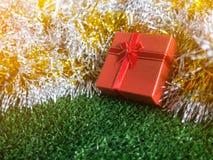 有红色丝带弓的红色礼物盒和银和金彩虹发光的装饰背景的金黄缝地方在绿草 图库摄影