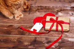 有红色丝带弓的被包裹的葡萄酒礼物盒和在木桌上的礼品券 库存照片