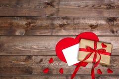 有红色丝带弓的被包裹的葡萄酒礼物盒和在木桌上的礼品券 图库摄影