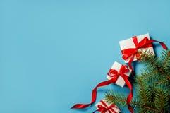 有红色丝带的圣诞礼物的白色箱子在蓝色背景平的被放置的拷贝空间的蓝色背景杉树分支 免版税库存图片