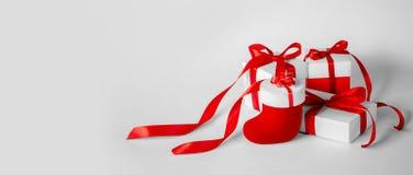 有红色丝带的圣诞礼物的白色箱子在轻的Backgroun 库存图片