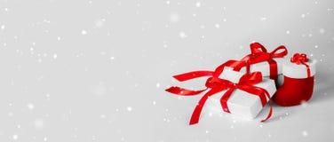 有红色丝带的圣诞礼物的白色箱子在轻的Backgroun 图库摄影