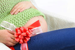 有红色丝带的孕妇的逗人喜爱的腹部 免版税库存图片