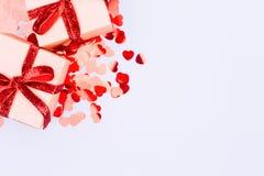有红色丝带的工艺箱子鞠躬并且闪烁心脏五彩纸屑 谷 免版税库存照片