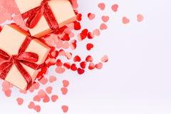 有红色丝带的工艺箱子鞠躬并且闪烁心脏五彩纸屑 谷 库存图片