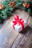 有红色丝带的白色当前箱子在木背景的杉木旁边 圣诞节礼物概念 库存照片