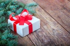 有红色丝带的白色当前箱子在木背景的杉木旁边 圣诞节礼物概念 库存图片