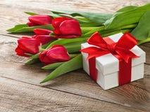 有红色丝带的箱子和郁金香花束  免版税库存照片