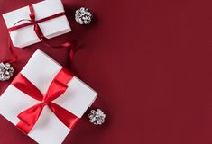 有红色丝带的,装饰,在白色和红色纸背景的杉木锥体圣诞礼物箱子 图库摄影
