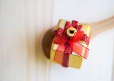 有红色丝带礼物的金黄箱子在木匙子 库存图片