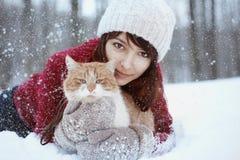 有红色举行和使用与小的蓬松猫的毛线衣的和帽子的美丽的女孩在冬天多雪的公园 宠物,舒适, christm 免版税库存图片