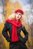 有红色伞、红色盖帽和红色围巾的美丽的时兴的女孩在公园 库存照片