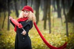 有红色伞、红色盖帽和红色围巾的美丽的时兴的女孩在公园 库存图片