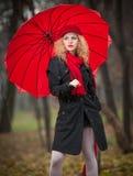 有红色伞、红色盖帽和红色围巾的美丽的时兴的女孩在公园 免版税库存图片