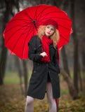 有红色伞、红色盖帽和红色围巾的美丽的时兴的女孩在公园 免版税库存照片