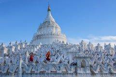 有红色伞的修士走在佛教寺庙的 免版税库存图片
