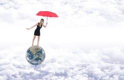 有红色伞的女孩作为气球代表的行星地球上 库存图片