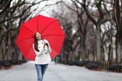 有红色伞的妇女走在秋天的公园的 免版税库存照片