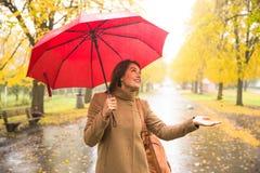 有红色伞的愉快的妇女走在雨的在美丽的秋天公园 库存照片