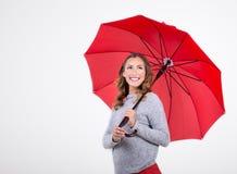 有红色伞的美丽的妇女 库存图片