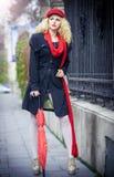 有红色伞的美丽的时兴的女孩在街道 图库摄影