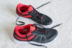 有红色修剪的跑鞋平在地板上 免版税库存照片