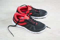有红色修剪的跑鞋平在地板上 库存图片