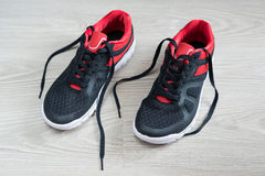 有红色修剪的跑鞋平在地板上 免版税库存图片