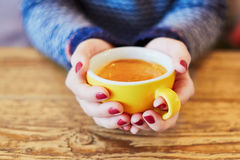 有红色修指甲和杯子的妇女手在木桌上的新鲜的热的咖啡 库存照片
