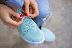 有红色修指甲的女性手打结了在体育鞋子的鞋带 免版税库存图片