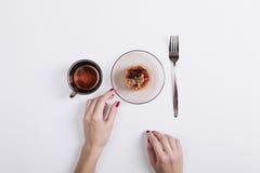 有红色修指甲的女性手采取从桌的蛋糕 免版税库存照片