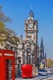 有红色公共汽车的爱丁堡反对clocktower在苏格兰 免版税库存照片