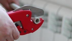 有红色剪刀的人切开了加热或者水的管子 聚丙烯架置系统 影视素材