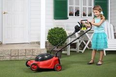 有红色割草机的愉快的逗人喜爱的小女孩 图库摄影