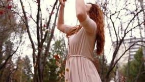有红色卷发投掷的叶子的愉快的妇女在秋天 快乐和激动的少妇获得乐趣在秋天公园 股票录像